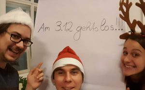 "Three people in Santa hats pose in front of a white board that reads ""Am 3.12. Gehts los!!!"""