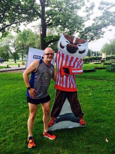 Darren DeMatoff posing with a mascot cutout in a park after running.