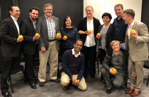 Ten people posing for a photo, all holding oranges and smiling.