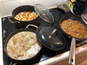 A stovetop with the pans cooking different Ugandan dishes.