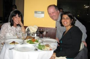 Three people at a table with food on it at a restaurant.