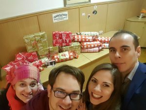 Four people smile for a selfie in front of a pile of wrapped Christmas presents.