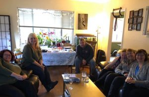 Six smiling people pose for a photo in a living room. The table in the background is set with a potluck and several flowering plants are growing in the window.