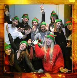 11 Wiener Wichtel elves smiling and posing for a photo wearing elf hats.