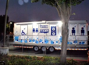 A Dignity on Wheels trailer parked in a parking lot next to a tree.