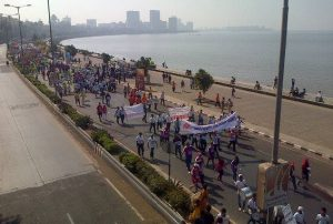 An aerial photo of runners holding banners as they run alongside the water.