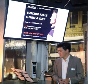 "A man giving a presentation on mental health. The screen behind him reads: ""AMHF. #KnowYourManFacts. Suicide kills 6 men a day. 3 out of 4 suicides are male. 2,348 Australian men took their own lives in 2017. Help us change this. Take action today at www.amhf.org/au/suicide"""