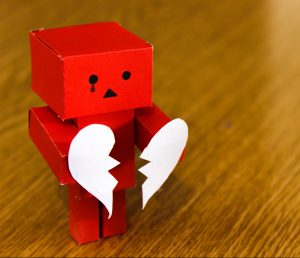 Photo of a red toy robot with a tear drawn onto its face holding two halves of a broken heart in its hands.