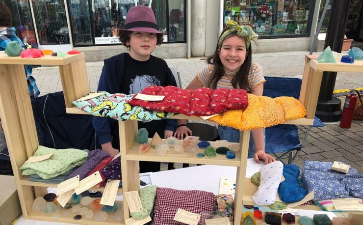 Two students selling handmade neck wraps at the 2019 Youth Entrepreneurship Market.