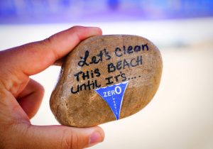 "A hand holding a rock painted with the words, ""Let's clean this beach until it's Zer0 Debris."""